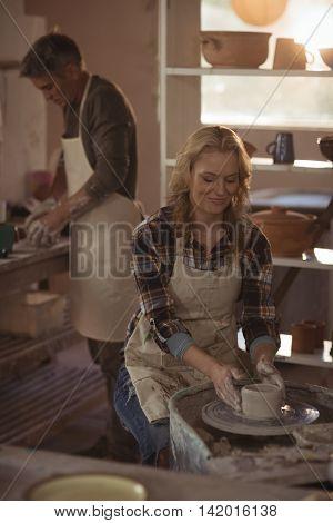Attentive female potter making pot in pottery workshop
