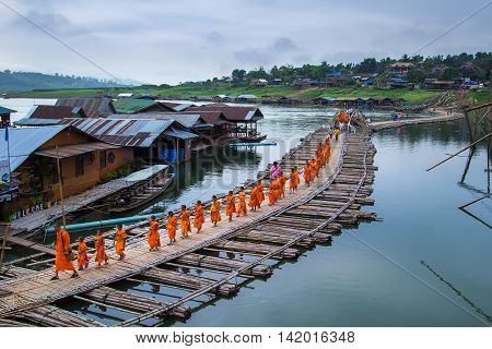 KANCHANABURI ,THAILAND - APRIL 18 2014: Buddhist monks walk on Bamboo Bridge the Sangkhla Buri River, Kanchanaburi, Thailand.