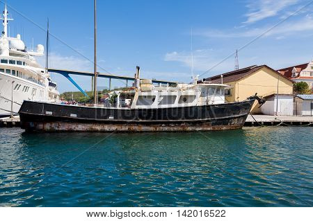 Rusty Black Boat by White Yacht in Curacao