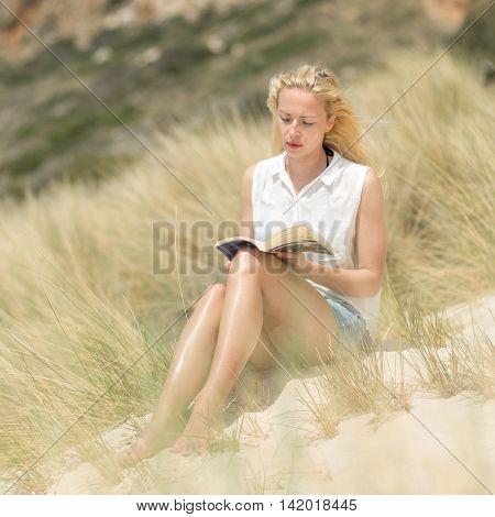 Woman Reading Book, Enjoying Sun On Beach.