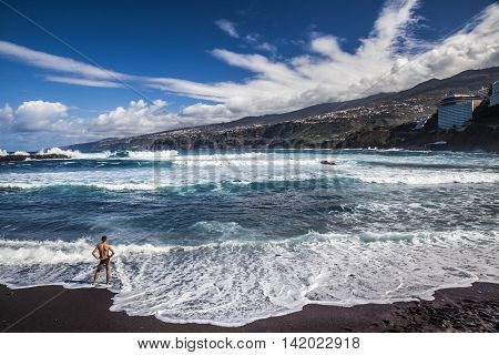 Man Watching Waves Smashing On The Beach