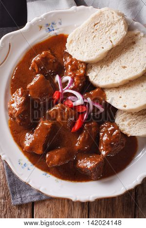 Thick Goulash With Dumplings On A Plate Close-up. Vertical Top View