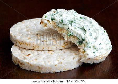 Pile Of Two And Half Eaten Puffed Rice Cakes Isolated On Dark Wood. With Chive And Herb Spread.
