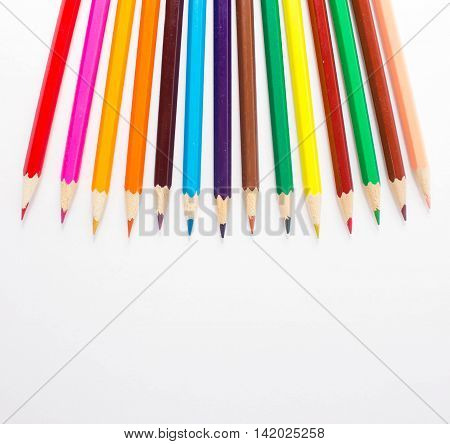 Colored pencils on white background. Schoolchild and student studies accessories. Back to school concept.