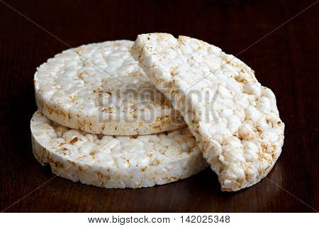 Pile Of Two And Half Puffed Rice Cakes Isolated On Dark Wood.