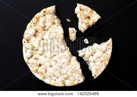 Broken Puffed Rice Cake From Above Isolated On Dark.