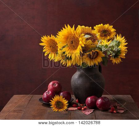 Autumn still life with Sunflowers and apples on old wooden table.