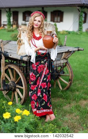 Pretty blonde woman in national ethnic ukrainian or polish folk traditional costume holding a clay jug and welcoming guests. Hospitality and ethnic tourism concept