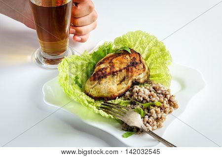 Breakfast with chicken, fresh herbs, a drink in a glass mug with buckwheat and chicken breast