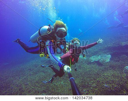 Underwater scuba diving selfie shot with selfie stick. Deep blue sea. Wide angle shot.