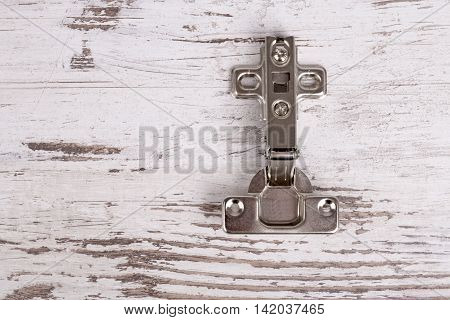 Adjustable steel hinge on grunge wooden background