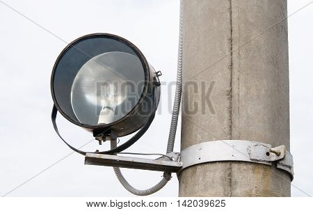 Old spotlight on a pole. electrical equipment