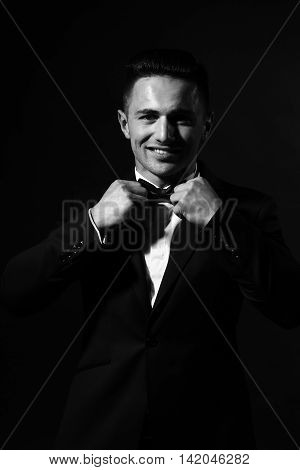 young handsome gentleman with smiling face in fashion black suit white shirt and bow tie in studio black and white