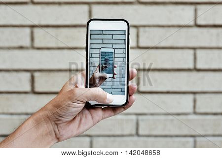 the hand of a young man taking a picture with its smartphone of his own hand taking a picture with its smartphone against a brick wall, as an infinity mirror effect