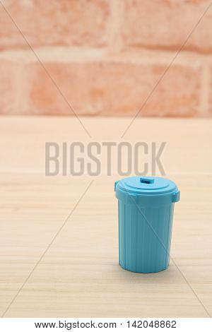 Blue plastic garbage bin in front of brick wall.