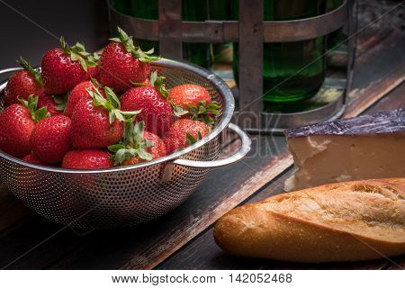 Fresh strawberries in stainless steel colander on a wood surface