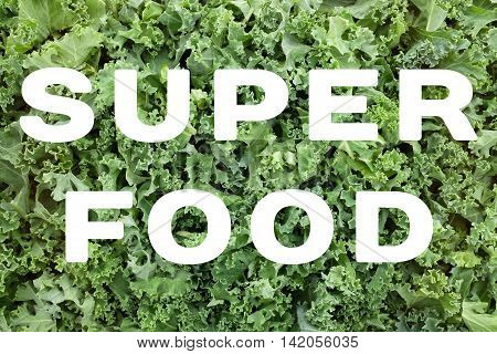 Superfood Text Over Shredded Kale Leaves Background