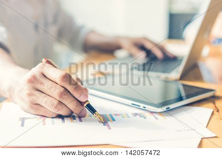Businessman analyzing investment charts. Accounting with soft focus vintage tone