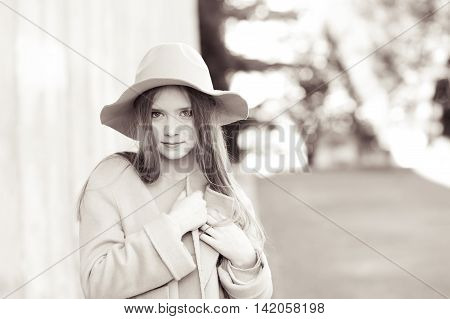 Stylish teen girl wearing trendy winter jacket and hat outdoors. Looking at camera. Black and white portrait.