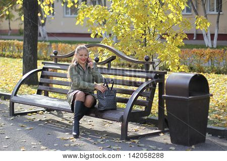 girl talking on the phone outdoors on a bench on a sunny autumn day