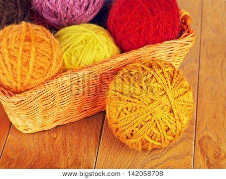 colorful yarn balls in wicker basket on wooden background