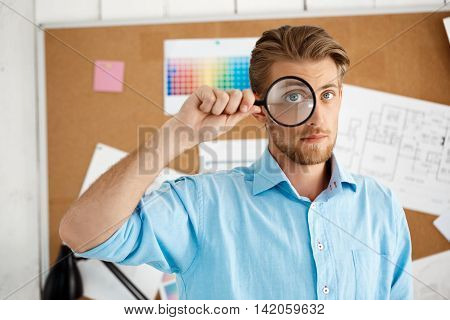 Picture of young handsome confident pensive businessman standing over cork board looking in camera through magnifier. White modern office interior background.
