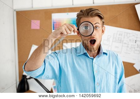 Picture of young handsome confident surprised businessman standing over cork board looking in camera through magnifier. White modern office interior background.