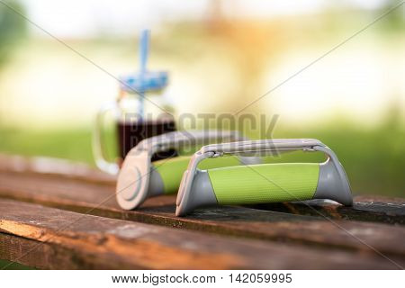 Small hand weights and smoothie on a wooden bench