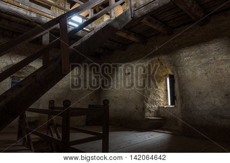 Dark room with stone walls window and wooden staircase