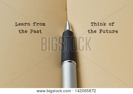 Open book with text on both sides and a pen in the middle