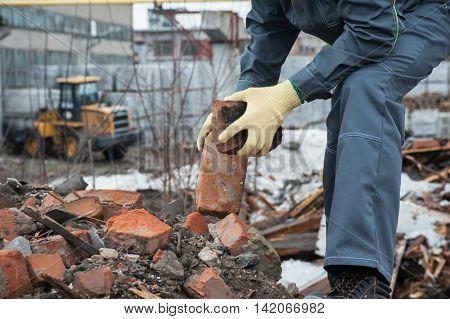 worker takes down blockages of broken bricks