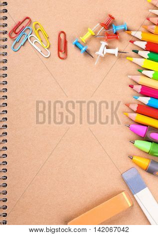 Notebook closeup with colored pencils erasers paperclips and buttons