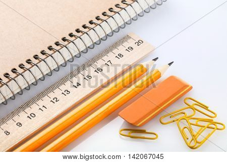 notebook eraser ruler pencil and paperclips on white background