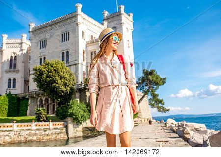 Young female traveler walking on the pier near Miramare castle in northeastern Italy