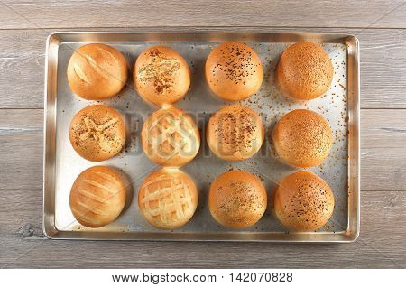 Breads on tray after oven on wooden background