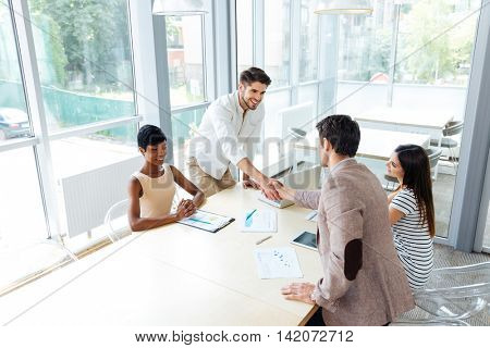 Two young businessmen shaking hands on business meeting in office