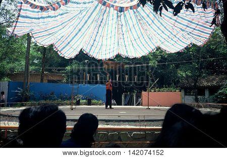 GUANGZHOU / CHINA - CIRCA 1987: A goat walks across a tight rope during a show at the Guangzhou Zoo.