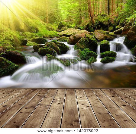 Mountain stream with wooden planks in the foreground. Spring forest with sunrays.