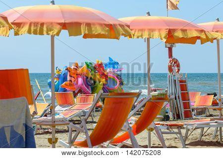 colorful deckchair umbrella and toys on an italian beach