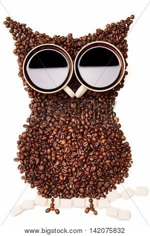 Coffee beans are laid out form Owl sitting on a branch of sugar cubes with the eyes of the cups