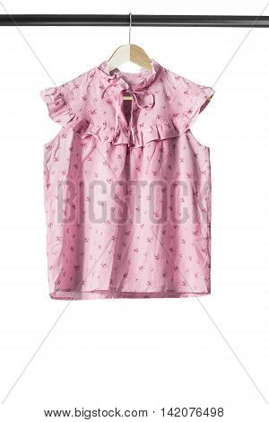 Pink sleeveless blouse on wooden clothes rack isolated over white