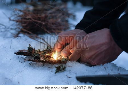Man lighting a fire in a dark winter forest preparing for an overnight sleep in nature warming himself with DIY fire. Adventure scouting survival concept.