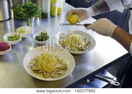 Preparetion dish of spaghetti with clams in a restaurant kitchen