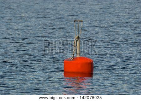 Flashing red buoy on the water surface of lake Saimaa in the Finnish city of Imatra.