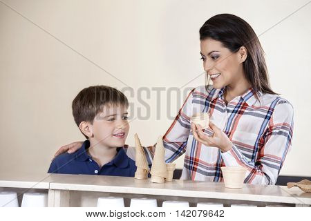 Mother And Son Choosing Between Cones  Cups