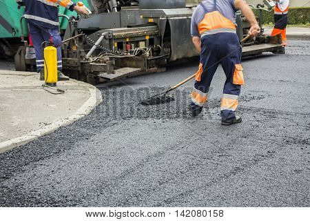 Workers on Asphalting paver machine during Road street repairing works