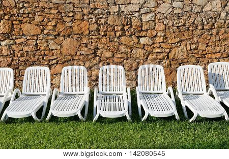 Row of white plastic sun loungers in front of a wall