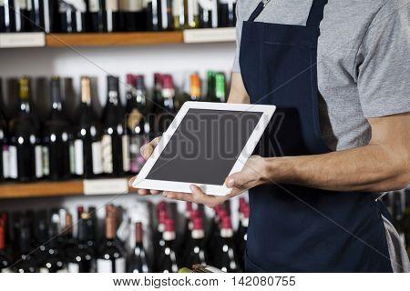 Salesman Showing Blank Digital Tablet In Wine Shop