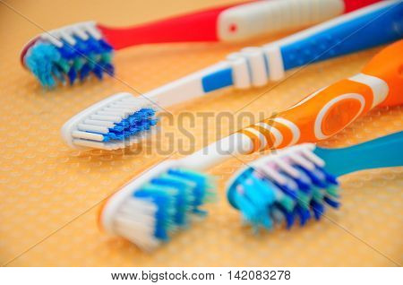 Set of toothbrushes on yellow nylon pad.