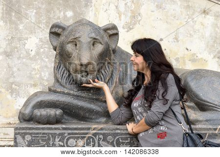A beautifl girl posing near a lion sculpture in a public square in Rome. She is touching the chin of the Lion